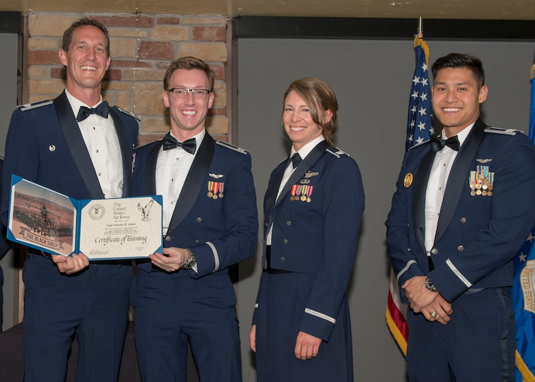 Lt. Col. Mark Sletten, 8th Fighter Squadron commander, presents Capt. Nicholas Atkins, 8th FS F-16 Basic Course graduate, with a certificate of training, May 4, 2019, at Club Holloman on Holloman Air Force Base, N.M. Eight Viper pilot students graduated from the 8th FS first F-16 B-Course, nearly eighty years since the squadron's induction on Nov. 20, 1940. (U.S. Air Force photo by Airman 1st Class Kindra Stewart)