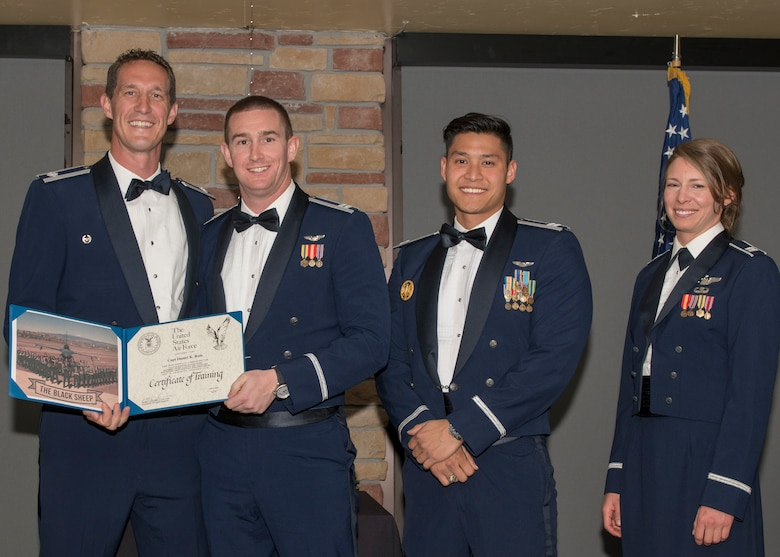Lt. Col. Mark Sletten, 8th Fighter Squadron commander, presents Capt. Daniel Rule, 8th FS F-16 Basic Course graduate, with a certificate of training, May 4, 2019, at Club Holloman on Holloman Air Force Base, N.M. Eight Viper pilot students graduated from the 8th FS first F-16 B-Course, nearly eighty years since the squadron's induction on Nov. 20, 1940. (U.S. Air Force photo by Airman 1st Class Kindra Stewart)