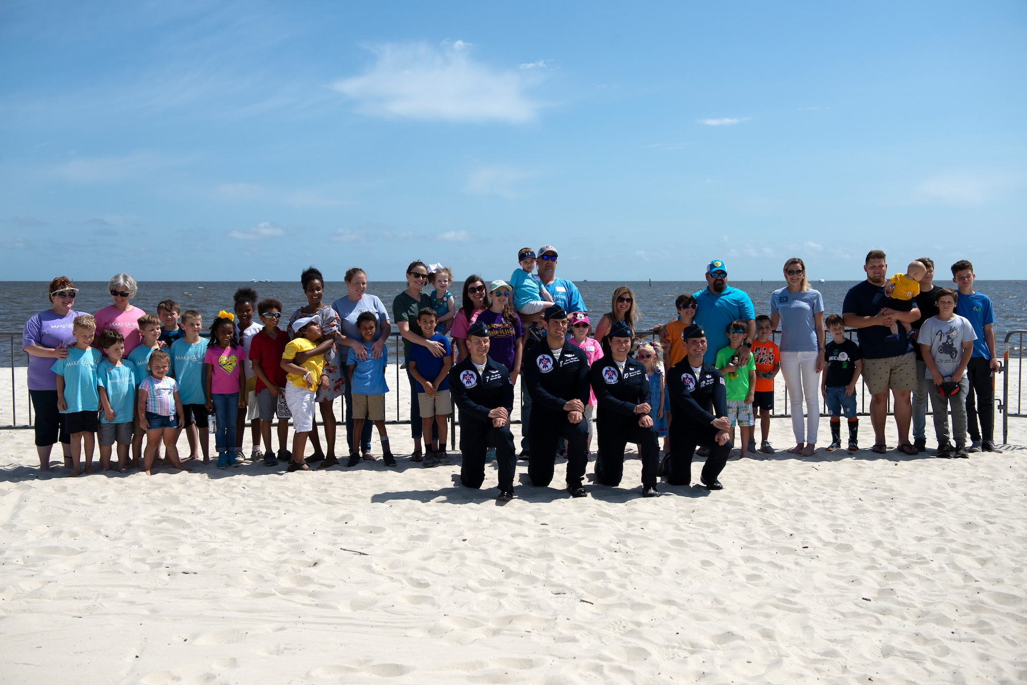 Make-A-Wish families pose for a group photo with the U.S. Air Force Thunderbirds in Biloxi, Mississippi, May 3, 2019. After viewing the Thunderbirds' practice session for the Keesler and Biloxi Air Show, the families had the opportunity to meet and speak with members of the Thunderbirds' team. (U.S. Air Force photo by Airman 1st Class Kimberly L. Mueller)