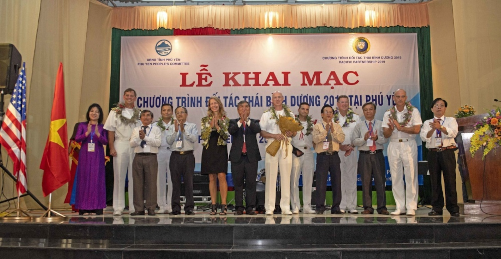 190506-N-NB178-1070 TUY HOA, Vietnam (May 6, 2019) Representatives from the local government of the Phu Yen Province pose for a group photo with Pacific Partnership 2019 leadership during the opening ceremony at the Hall of the Provincial Labor Union during Pacific Partnership 2019. Pacific Partnership, now in its 14th iteration, is the largest annual multinational humanitarian assistance and disaster relief preparedness mission conducted in the Indo-Pacific. Each year, the mission team works collectively with host and partner nations to enhance regional interoperability and disaster response capabilities, increase stability and security in the region, and foster new and enduring friendships in the Indo-Pacific. (U.S. Navy photo by Mass Communication Specialist 1st Class Tyrell K. Morris)