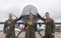 U.S. Air Force 1st Lt. Jeffery, Airman 1st Class Jacqueline and  Dallas, 15th Attack Squadron MQ-9 Reaper sensor operators from Creech Air Force Base, Nevada, pose for a photo with an MQ-9 Reaper Unmanned Aerial Vehicle during the Keesler and Biloxi Air and Space Show on Keesler Air Force Base, Mississippi, May 4, 2019. TThe U.S. Air Force Thunderbirds headline the unique, one-of-a-kind joint air show, May 4-5, that is geographically separated from the base and the city's beach front. (U.S. Air Force photo by Andre Askew)