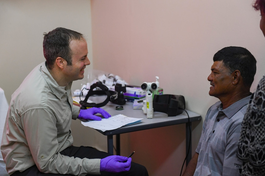 U.S. Air Force Lt. Col. James Richard Townley, ophthalmologist from Joint Base Elmendorf-Richardson, Alaska, talks with a patient during the New Horizons exercise 2019 at Port Mourant, Guyana, May 3, 2019.
