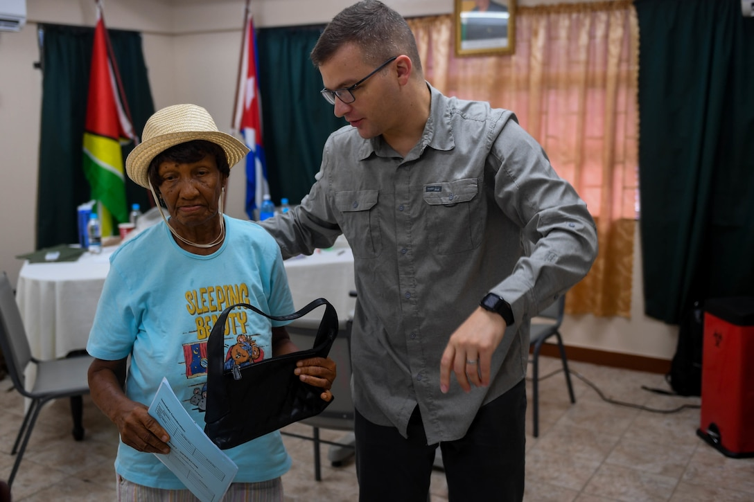 U.S. Air Force Maj. Andrew Lewis, ophthalmologist from Joint Base San Antonio-Lackland, Texas, guides a Guyanese patient to the next examine station during New Horizons 2019, Port Mourant, Guyana, May 3, 2019.