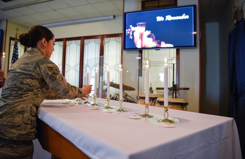 An Airman places a candle in a holder during a remembrance ceremony on Kunsan Air Base, Republic of Korea, May 2, 2019. The candle lighting portion of the ceremony was in remembrance of the 6 million Jews and other minorities who were killed during the Holocaust. (U.S. Air Force photo by Capt. Remoshay Nelson)