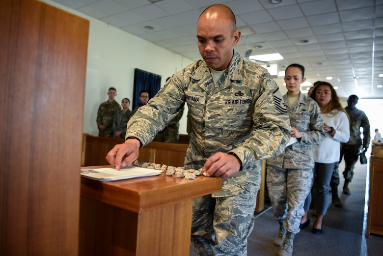 Master Sgt. Michael Kumiyama, 8th Force Support Squadron career assistant advisor, places a story of the Holocaust victims and a pebble on a table during Kunsan Air Base's Holocaust Remembrance Ceremony at the Base Chapel on May 2, 2019. The ceremony is part of the national Days of Remembrance observance established by Congress to commemorate the Holocaust. This year, it is observed from April 28 through May 5. (U.S. Air Force photo by Capt. Remoshay Nelson)