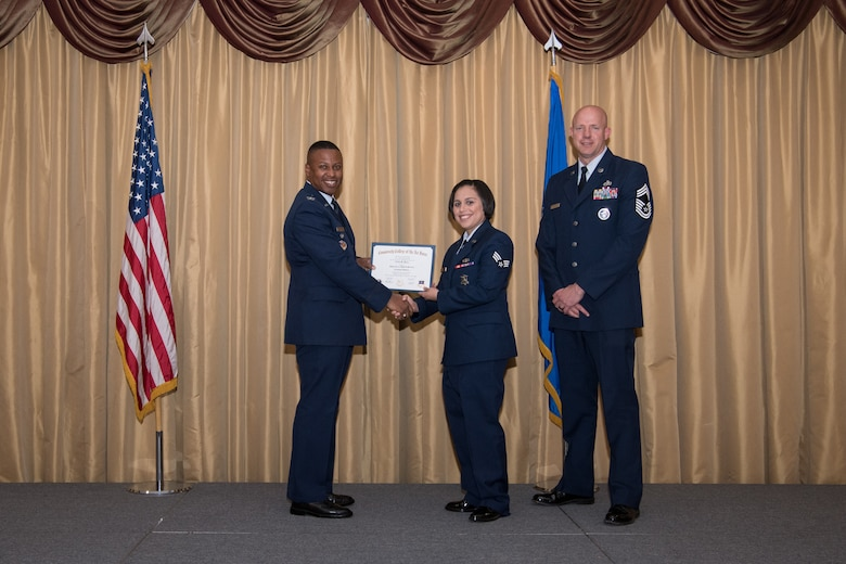 Senior Airman Erika B. Perez, 514th Security Forces Squadron member, 514th Air Mobility Wing, Joint Base McGuire-Dix-Lakehurst, N.J., is presented with his Community College of the Air Force Associates Degree by Col. Adrian R. Byers, 514th AMW vice commander, May 3, 2019.