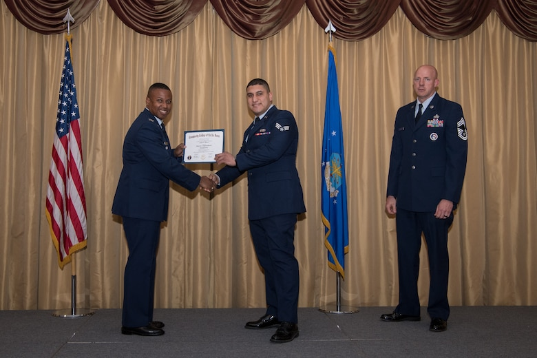 Senior Airman Pablo A. Altiery, 88th Aerial Port Squadron air transportation specialist, 514th Air Mobility Wing, Joint Base McGuire-Dix-Lakehurst, N.J., is presented with his Community College of the Air Force Associates Degree by Col. Adrian R. Byers, 514th AMW vice commander, May 3, 2019.