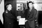 A Defense Supply Agency employee with the Data Systems Automation Office in Columbus, Ohio, receives an award for saving DoD money through value engineering in the 1960s. Courtesy photo