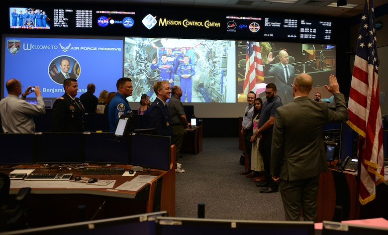 Dr. Benjamin Johansen, stands with his right hand raised as he is administered the commissioning oath by Army Lt. Col. Anne McClain, an astronaut on the International Space Station, 210 miles above earth. Johansen is joining the Air Force Reserve as a flight surgeon and will wear the rank of a captain, but as a civilian he is a flight surgeon with NASA and is assigned as one of two flight surgeons for McClain. (Air Force photo/Master Sgt. Chance Babin)
