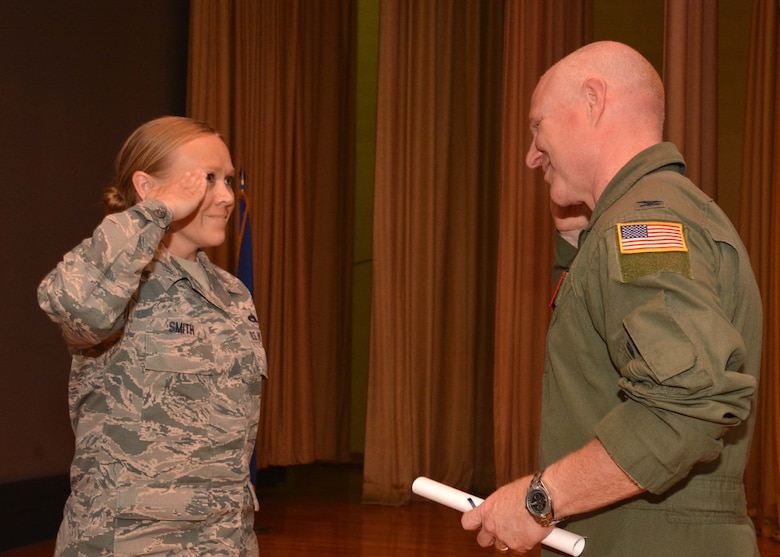 Master Sgt. Jessica Smith, 507th Operations Group career assistance advisor, salutes Col. Miles Heaslip, 507th Air Refueling Wing commander, during the May UTA commander's call at the base theater, May 5, 2019, Tinker Air Force Base, Oklahoma. Smith was recognized for receiving her Community College of the Air Force degree. (U.S. Air Force photo by Senior Airman Mary Begy)