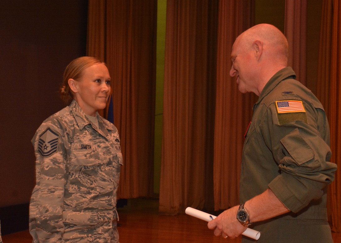 Master Sgt. Jessica Smith, 507th Operations Group career assistance advisor, speaks with Col. Miles Heaslip, 507th Air Refueling Wing commander, during the May UTA commander's call at the base theater, May 5, 2019, Tinker Air Force Base, Oklahoma. Smith was recognized for receiving her Community College of the Air Force degree. (U.S. Air Force photo by Senior Airman Mary Begy)