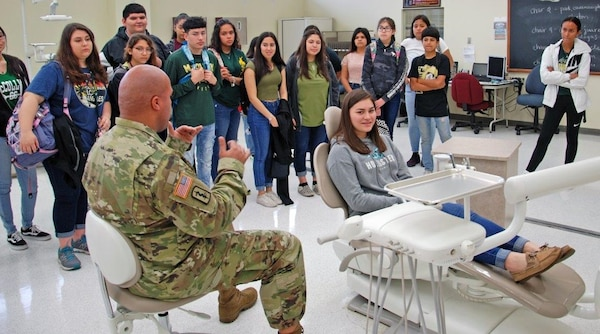 Staff Sgt. James Mcalister, NCOIC Dental Department, Preventative Medicine, briefs students on the training and equipment used in the dental program while Taetum, a freshman in McCollum High School's health science class sits in the hot seat. Taetum plans to be a cardiac thorasic surgeon after college.