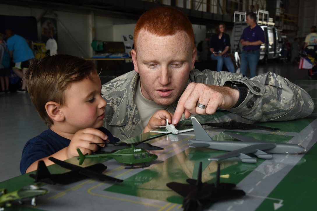 An airman uses a toy airplane to teach a young child about air traffic control.