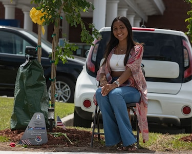 Valeria Colon, daughter of Master Sgt. Victor Colon, poses for a portrait next to a tree planted in her father's honor after a memorial ceremony May 2, 2019, in Port Wentworth, GA. The event paid homage to the lives of the nine Puerto Rican Air National Guard Airmen who lost their lives when their C-130 Hercules, assigned to the 156th Airlift Wing, crashed May 2, 2018.