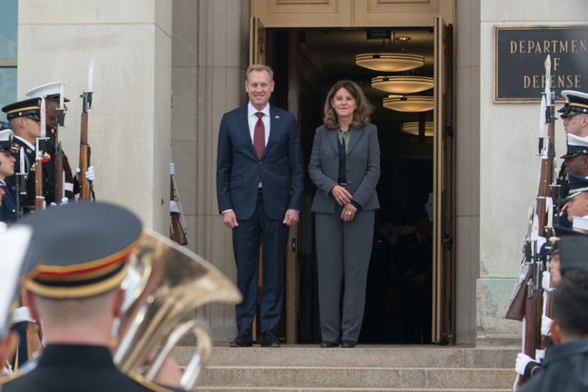 Acting Defense Secretary Patrick M. Shanahan stands at the top of steps with the Colombian Vice President; service members stand on each side.