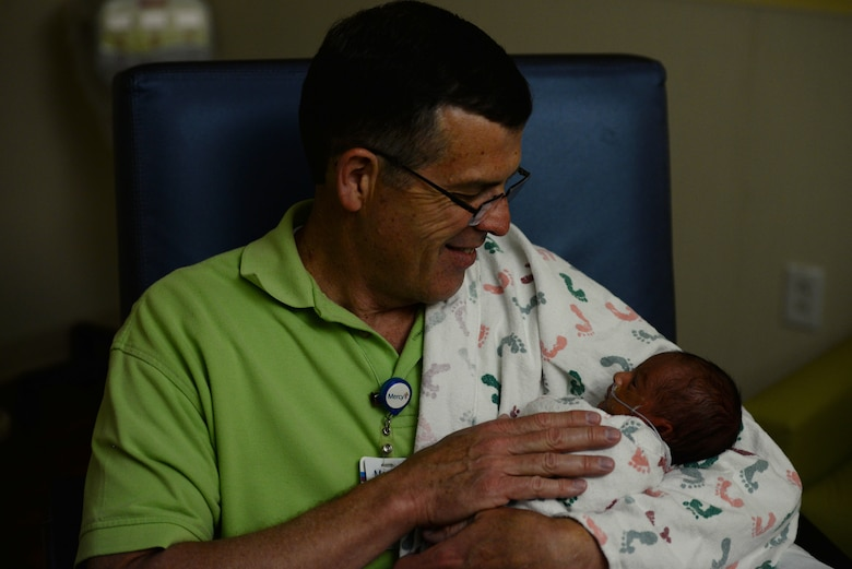 "David Young, 60, Air Mobility Command current operations air mobility analyst and retired Air Force pilot, holds the premature grandson of a retired Air Force member while in the Neonatal Intensive Care Unit at Mercy Hospital in St. Louis, April 19, 2019. Young has been a volunteer for the hospital's ""cuddler program"" for a year and a half. He has eight children of his own and was interested in the program because his youngest child, now 17 years old, was born eight weeks early. (U.S. Air Force photo by Airman 1st Class Miranda Simpson)"