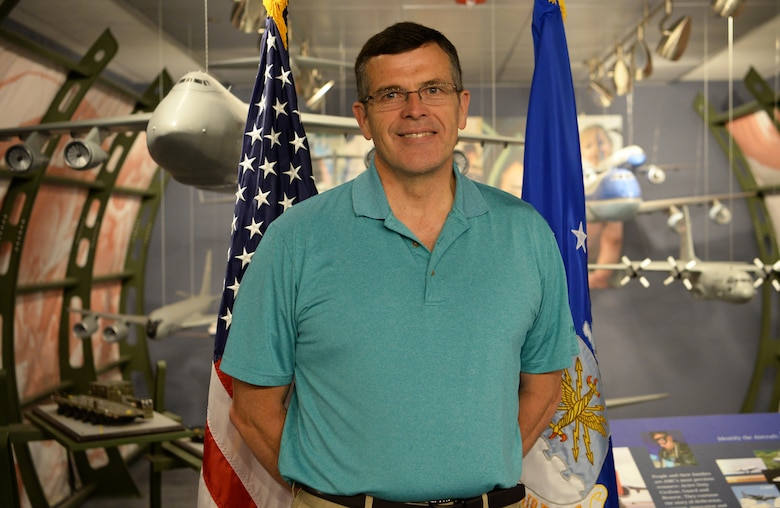 David Young, 60, Air Mobility Command current operations air mobility analyst and retired Air Force pilot, proudly stands by a model of a C-5 Galaxy at Scott Air Force Base, Ill., April 30, 2019. Young used to fly the aircraft when he was a pilot, and he helped build the display back when it was first installed. In his free time, Young volunteers in the Neonatal Intensive Care Unit at Mercy Hospital in St. Louis. (U.S. Air Force photo by Airman 1st Class Miranda Simpson)