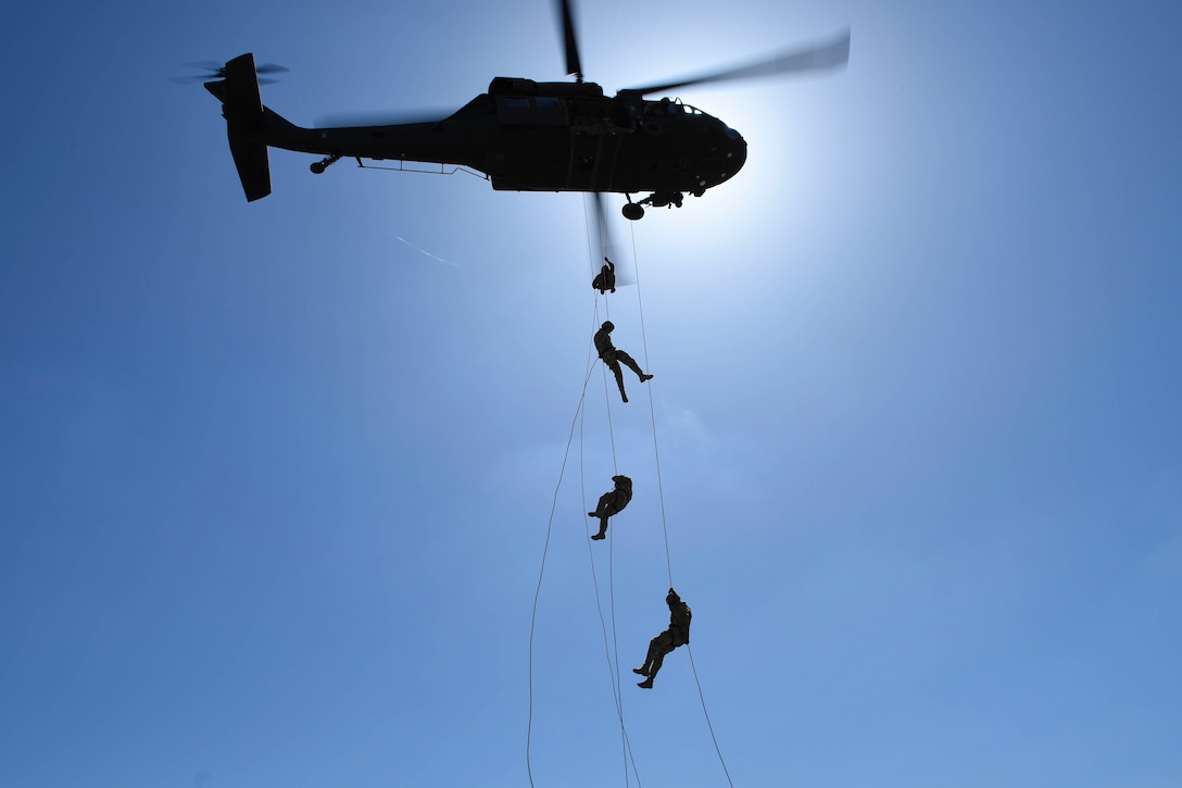Four airmen rappel out of a helicopter.