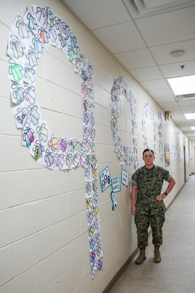 """Sgt. Brittany Callaway stands in front of a Sexual Assault Awareness Month display at Marine Wing Support Detachment 273 aboard Marine Corps Air Station Beaufort, May 1. Callaway had the Marines of the detachment show their support of SAAPM by decorating 998 dog tags to bring awareness to the 998 sexual assaults reported in FY17. """"We talked about how those numbers have gone up, but because Marines are more aware and are more comfortable reporting it because of the education and the climate of their units,"""" Callaway said. """"This was also a way to start a sometimes uncomfortable conversation."""" Callaway is a sexual assault prevention and response advocate with MWSD-273."""