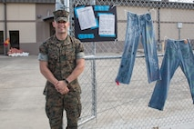 1st Lt. Jacob Ridings stands in front of a Denim Day display that was set up for a Sexual Assault Awareness Month campaign aboard Marine Corps Air Station Beaufort, May 1. Denim Day began nearly 20 years ago after a rapist's conviction was overturned by the Italian Supreme Court because the justices felt that since the young woman was wearing tight jeans, she must have assisted the rapist in removing them. The next day, the women in Italian Parliament came to work wearing denim, and now annually one Wednesday in April is honored as Denim Day. This was one of several awareness displays set up around Marine Wing Support Detachment 273. Ridings is a SAPR advocate with MWSD-273. (U.S. Marine Corps photo by Cpl. Ashley Phillips)