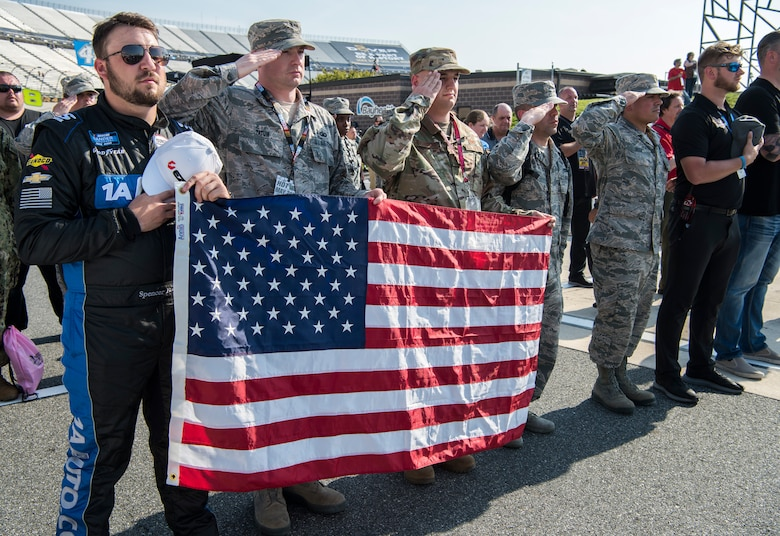 Honorary pit crew members, NASCAR drivers and pit crew members salute during the singing of the national anthem before the start of the JEGS 200 race May 3, 2019, at Dover International Speedway in Dover, Del. NASCAR teams partner with Dover Air Force Base to offer Dover service members the opportunity to participate as a team member during the race. Each race, roughly 35 service members attend as honorary pit crew members. (U.S. Air Force photo by Senior Airman Christopher Quail)