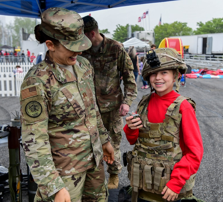 Capt. Michelle Petry, 436th Civil Engineer Squadron Explosive Ordnance Disposal flight commander, helps Reagan Fesel don military gear May 4, 2019, at Dover International Speedway, Dover, Del. The EOD technicians, firefighters, and Security Forces Squadron members set up static displays to provide a hands-on experience to those attending the races.  (U.S. Air Force photo by Senior Airman Christopher Quail)