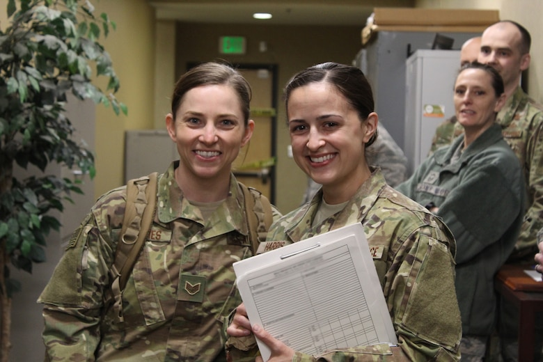 Staff Sgts. Brittany Toennies and Kayla Harris, 718th Intelligence Squadron imagery analysts, are greeted in the Valley of the Eagles by the 755th Intelligence, Surveillance and Reconnaissance Group leadership, 718th IS members and the 497th Intelligence, Surveillance and Reconnaissance Group's moral dog, Sam, after returning home from their deployment in April. (Courtesy photo)