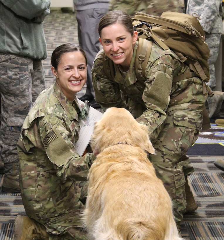 Staff Sgts. Brittany Toennies and Kayla Harris, 718th Intelligence Squadron imagery analysts, are greeted by the 497th Intelligence, Surveillance and Reconnaissance Group's moral dog, Sam, after returning home from their deployment in April. The Airmen were also greeted in the Valley of the Eagles by the 755th Intelligence, Surveillance and Reconnaissance Group leadership and 718th IS members. (Courtesy photo)