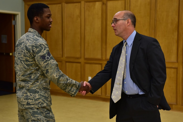 An Airman shakes the hand of the guest speaker during a Holocaust rembrance service.