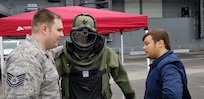 Tech. Sgt. Jared Doherty, 514th  Explosive Ordnance Disposal team lead, talks about the purpose and capabilities of a bomb suit with an Air Force Convention attendee at the Intrepid Sea, Air & Space Museum during the Air Force Convention in New York City, May 4, 2019.