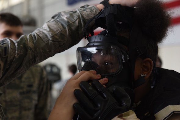 A girl wearing protective military gear puts on a gas mask