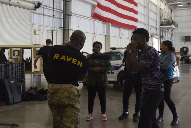 "A man wearing a black shirt saying ""RAVEN"" on his back says stands next to a high school student with his fists up in a sparring position."