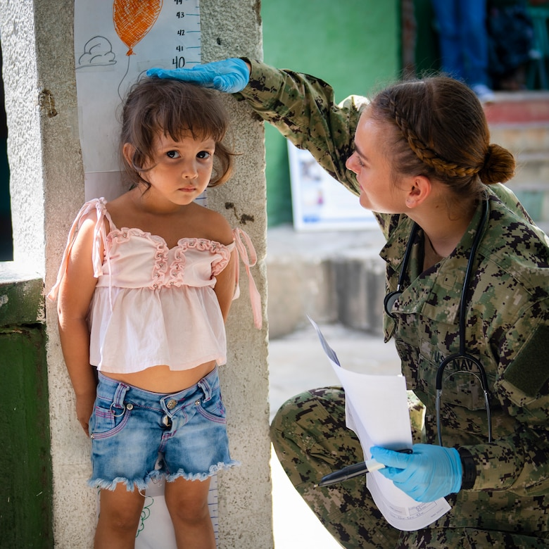 A sailor measures a girl's height.