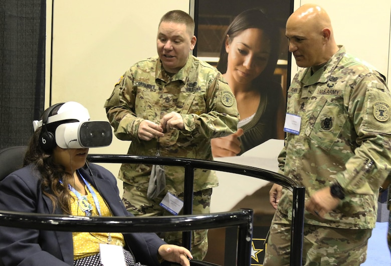 MSB Exhibitors Sgt. 1st Class Daniel Carpenter (center) and Sgt. 1st Class Ty Ramon (right) guide a participant through a 360 degree interactive display focused on tandem skydiving with the Army Parachute Team.