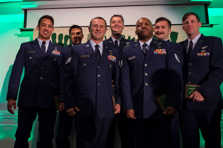 Pararescuemen from the 48th Rescue Squadron (RQS) and aircrew from the 41st RQS, pose for a photo during the banquet celebrating the 50th reunion of the Jolly Green Association (JGA), May 4, 2019, in Fort Walton Beach, Fla. The JGA presented Airmen from the 41st RQS and the 48th RQS with the Rescue Mission of the Year award; the only non Air Force award recognized by the Air Force. (U.S. Air Force Photo by Staff Sgt. Janiqua P. Robinson)