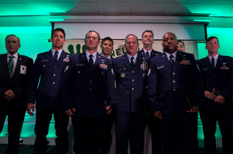 Airmen from the 41st and 48th Rescue Squadron's (RQS) pose for a photo with Air Force Chief of Staff Gen. David L. Goldfein, during the banquet celebrating the 50th reunion of the Jolly Green Association (JGA), May 4, 2019, in Fort Walton Beach, Fla. The JGA presented Airmen from the 48th and 41st RQS with the Rescue Mission of the Year award; the only non Air Force award recognized by the Air Force. (U.S. Air Force Photo by Staff Sgt. Janiqua P. Robinson)