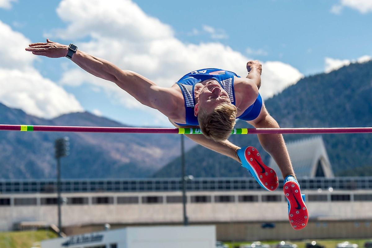 An athlete jumps over a horizontal bar.