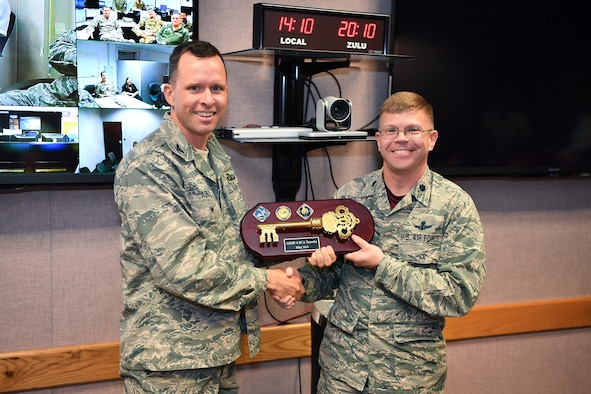 Lt. Col. Armon Lansing (right), 4th Space Operations Squadron commander, accepts the key from Col. David Ashley, Space and Missile Center AEHF program manager, signifying the handoff of the Advanced Extremely High Frequency-4 satellite to the 4th SOPS at Schriever Air Force Base, Colorado, May 3, 2019. AEHF-4 joins the squadrons other military satellite communication satellites supporting space and intelligence, nuclear and defense, theater mission defense and special operations. This is the fourth satellite the squadron commands and controls, with two more launces planned. (U.S. Air Force photo by Kathryn Calvert)
