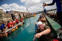 """The Single Marine Program dragon boat team pushes off the dock to begin their race during the 45th Annual Naha Dragon Boat Race May 5, 2019, at Naha Port, Okinawa, Japan. Local and military communities participated in the famous race, also known as the """"Haarii."""" The SMP team placed first in their preliminary heat."""
