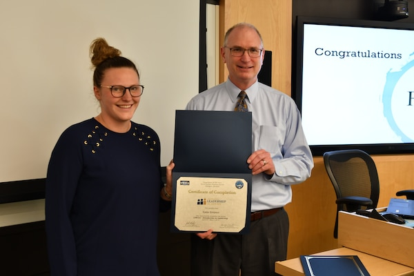IMAGE: Gill Goddin, Naval Surface Warfare Center Dahlgren Division (NSWCDD) chief engineer, presents a certificate to a NSWCDD Leadership 101 graduate.