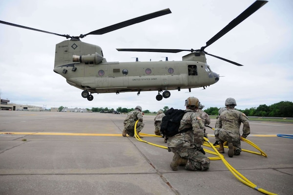 Members of the Downed Aircraft Recovery Team (DART) with Company B, 834th Aviation Support Battalion brace as a UH-47 Chinook helicopter approaches for a sling load operation May 4, 2019 at the Army Aviation Support Facility #2 in Tulsa, Oklahoma. The exercise involves lifting the body of a Chinook helicopter with another Chinook in order to train Soldiers in the recovery of downed aircrafts in combat.