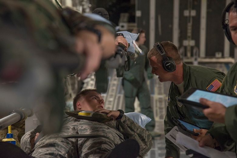 U.S. Air Force Senior Airman Matthew Wright, charge medical technician with the 315th Aeromedical Evacuation Squadron at JB Charleston, South Carolina, checks on his mock paitent, Civil Air Patrol cadet Elkin, during a National Disaster Management System exercise May 7, 2019, en route to Greenville, S.C. Approximately 30 CAP cadets volunteered as mock patients to assist in the NDMS training flight that helped the 315AES prepare for real life scenerios.