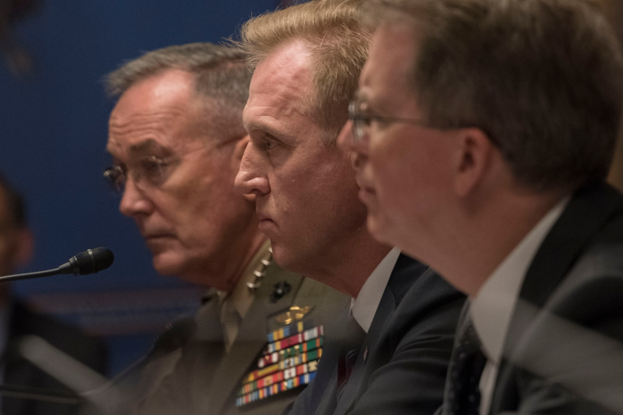 Three defense leaders sit together at a table.