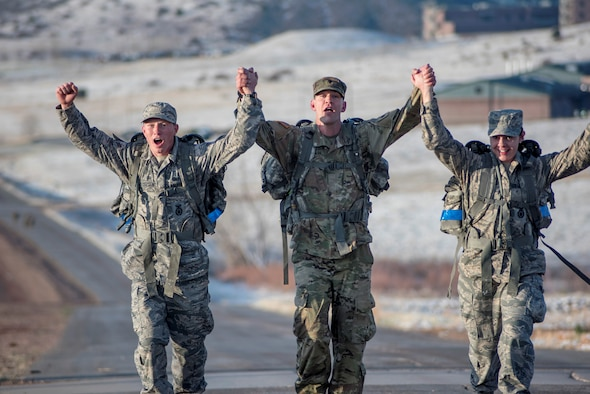3 participants in the Best Warrior Competition hold hands high in victory