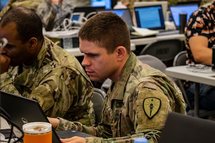 A soldier works at a computer station.