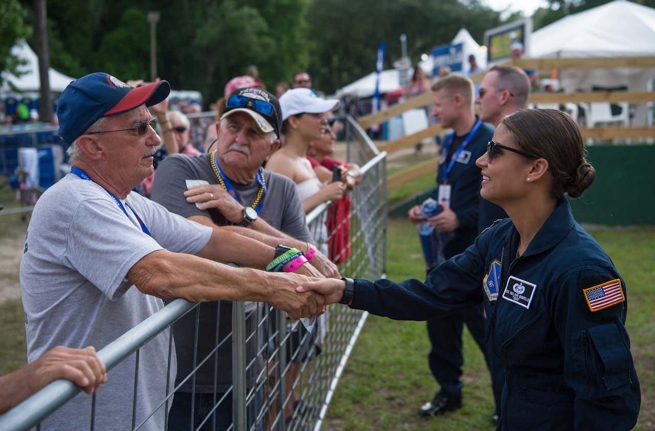 A female airman shakes hands with an older man on the opposite side of a fence. Others can be seen doing the same in the background at a fair.