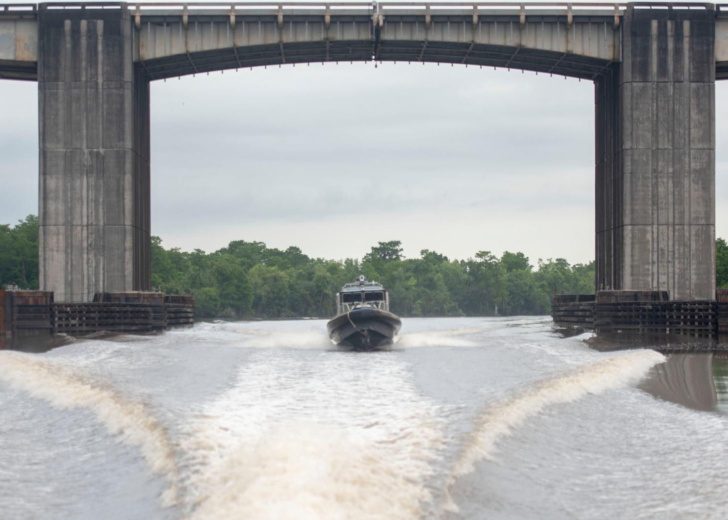 a boat transits a river under a bridge