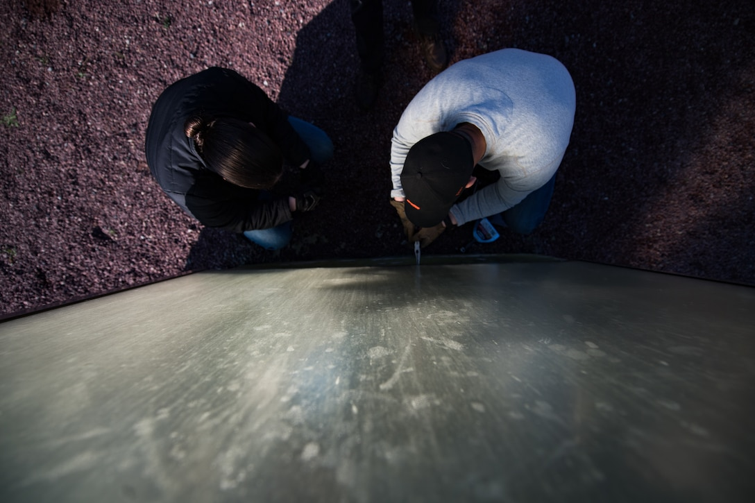 U.S. Air Force Airman 1st Class Rachel Miller, 435th Construction Training Squadron power production journeyman, and Staff Sgt. Matthew Evans, 435th CTS structural contingency instructor, disassemble a display case, housing a WWII aircraft engine, at a memorial in Picauville, France, April 30, 2019. Before arriving to Picauville, the 435th CTS team prepared a new display case to replace the damaged one. (U.S. Air Force photo by Staff Sgt. Devin Boyer)