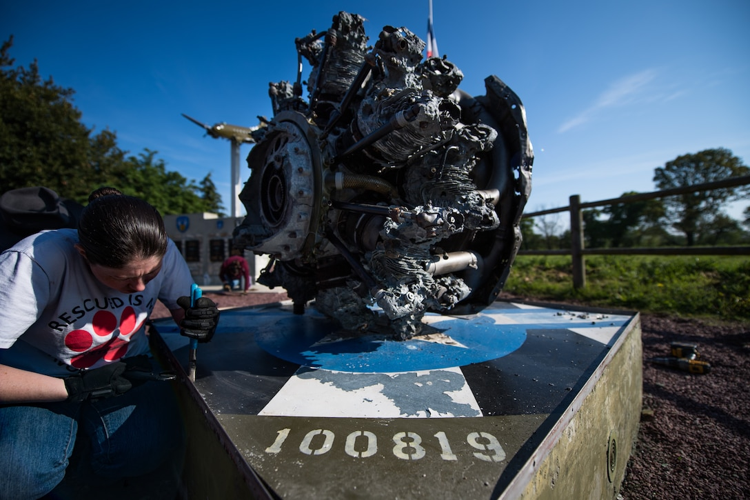 "U.S. Air Force Airman 1st Class Rachel Miller, 435th Construction Training Squadron power production journeyman, loosens a screw attached to the pedestal of a WWII aircraft display at a memorial in Picauville, France, April 30, 2019. The ""100819"" painted on the pedestal represents the aircraft number the engine belonged to. (U.S. Air Force photo by Staff Sgt. Devin Boyer)"