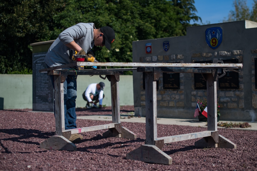 U.S. Air Force Staff Sgt. Matthew Evans, 435th Construction Training Squadron structural contingency instructor, brushes a metal frame at a WWII memorial in Picauville, France, April 30, 2019. The frame was used to anchor a display case holding an aircraft engine that was shot down on D-Day. (U.S. Air Force photo by Staff Sgt. Devin Boyer)